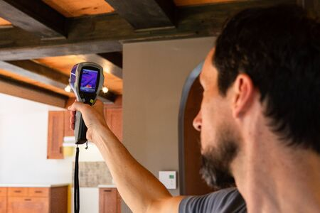 Indoor damp & air quality (IAQ) testing. An indoor environment quality (IEQ) assessor is seen at work, using a digital thermography device during an in-depth inspection of a domestic building.