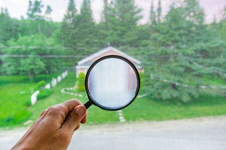 Indoor damp & air quality (IAQ) testing. A first person perspective, holding a magnifying glass in front of a window, looking towards a detached garage and green garden, with blurry background. Stockfoto - 131715665