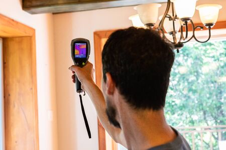 Indoor damp & air quality (IAQ) testing. A close up and rear view on the head of a home inspector with short black hair, using a handheld device to check the temperature and insulation in a home.