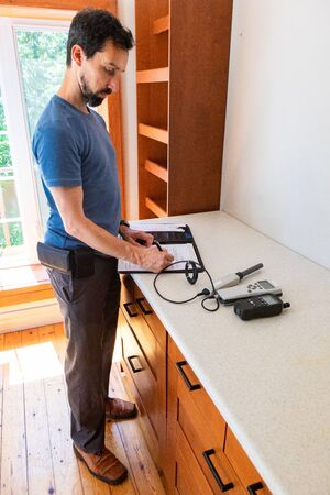 Indoor damp & air quality (IAQ) testing. An indoor environmental quality assessor is seen inside a residential property, taking readings from digital devices and writing down results on paperwork.