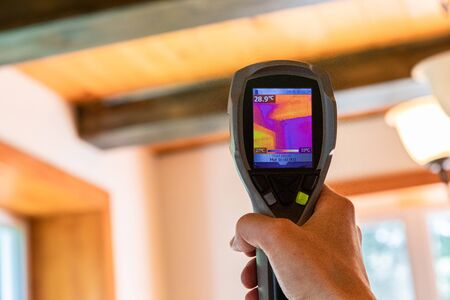 Indoor damp & air quality (IAQ) testing. An infrared thermal imaging device is seen in use, close up during an indoor environmental quality and regulation assessment, with copy space.