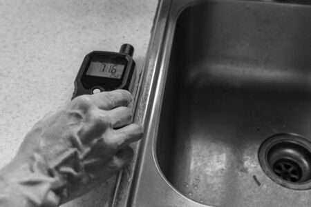 Indoor damp & air quality (IAQ) testing. A close up and monochrome view on the hand of an indoor environmental quality assessor, taking readings from an electronic meter by a kitchen sink. Imagens