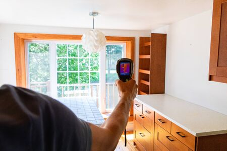 Indoor damp & air quality (IAQ) testing. An over the shoulder view of an indoor environmental quality (IEQ) assessor at work inside a kitchen, using a thermal vision device to check home insulation.