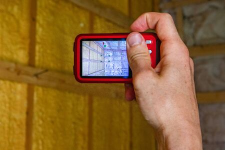 Indoor damp & air quality (IAQ) testing. An point of view perspective of indoor environmental quality (IEQ) surveyor at work, using a digital camera to photograph glass fiber insulated walls.