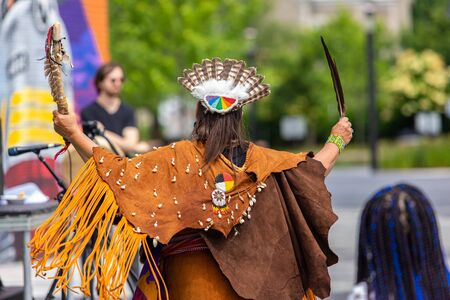 Entertainment at multicultural festival. A close up and rear view of a woman in traditional Native American clothing, holding sacred eagle feather during a music event celebrating traditional culture. 版權商用圖片