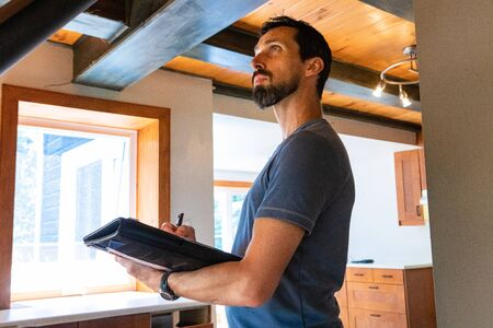 Indoor damp & air quality (IAQ) testing. A close up and side view of a tall caucasian male with short black hair and beard, inspecting a home during an indoor environmental quality assessment.