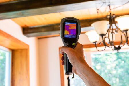 Test dell'umidità interna e della qualità dell'aria (IAQ). Una termocamera portatile a infrarossi viene vista in primo piano, controllando i livelli di isolamento all'interno di una casa domestica con travi di legno sfocate sullo sfondo.