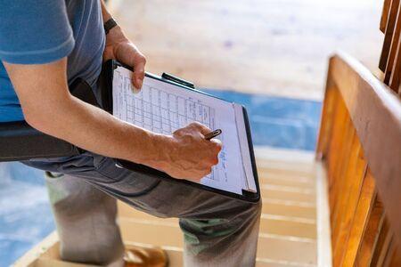 Prüfung der Feuchte und Luftqualität (IAQ) in Innenräumen. Eine Nahaufnahme und hohe Betrachtungswinkel eines professionellen Mannes mit blauem T-Shirt, der während einer Hausinspektion Formulare ausschreibt und auf einer Treppe mit Kopienraum steht.