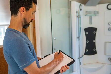 Testen voor binnenvochtigheid en luchtkwaliteit (IAQ). Een professionele man wordt van dichtbij en van opzij gezien, met behulp van een pen en papier om aantekeningen te maken tijdens en de beoordeling van de kwaliteit van het binnenmilieu in een badkamer. Stockfoto