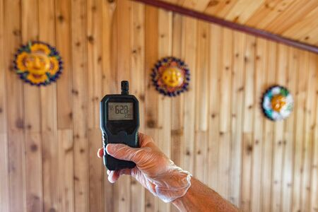 Indoor damp & air quality (IAQ) testing. A digital air monitoring device is seen close up in the hand of a person, showing a high reading to indicate airborne allergens, particles and CO2 in the home. Banco de Imagens
