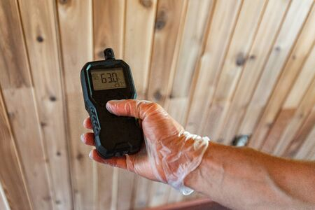 Indoor damp & air quality (IAQ) testing. A professional home inspector is seen close-up, using a handheld device to check for pollutants during an indoor environmental quality (IEQ) assessment.