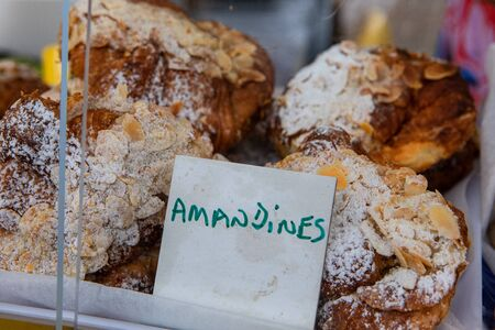 Baked goods at outdoor agriculture fair. A closeup view of freshly baked amandines (almond pastries), displayed on a market stall selling sweet treats during a local farmers market. Stok Fotoğraf