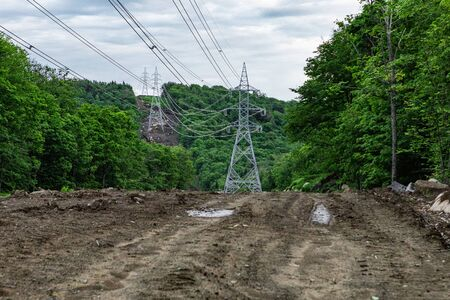Electricity pylons in natural landscape. A wide angle view of electric transmission towers running through a dense forest, felled trees and a muddy track make way for power infrastructure.