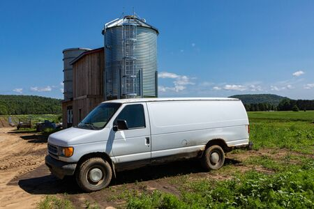 Traditional transport at organic farm. A large white cargo van is viewed from the side with room for text, parked up by farm buildings in rural farmland beneath a clear blue sky.