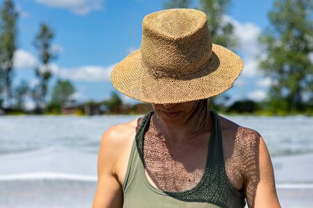 Farmhands tend crops at ecological farm. A close up and front view of a young caucasian woman, wearing a woven brimmed hat as she helps out on a rural farm, with copy space.