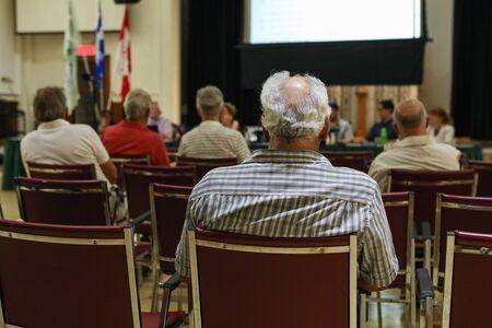Mensen wonen de lokale gemeentehuisvergadering bij. Een close-up en achteraanzicht van een oudere man die binnenshuis zit tijdens een wetgevingsvergadering van het stadhuis, wazige aanwezigen worden op de achtergrond gezien met kopieerruimte. Stockfoto