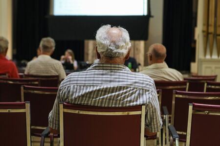 People attend local town hall meeting. A close up and rear view on the back of an elderly mans head, with grey hair and bald spot, during a village council assembly. Stock fotó