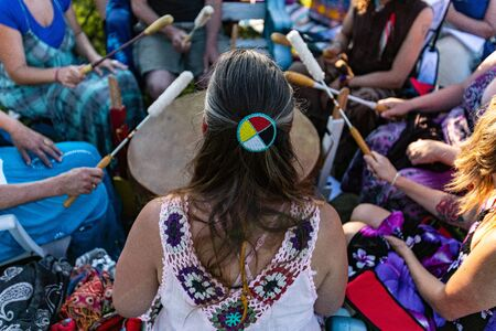 Sacred drums during spiritual singing. A colorful group of people are seen from a high angle, as they perform Native American music using a mother drum and beaters in a public park.