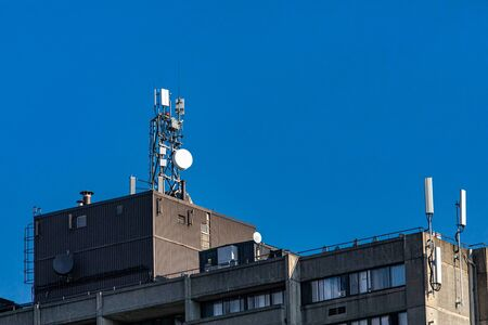 View of the top of an industrial building equipped with various GPS, cellphone, telecommunication equipment, with perfect blue sky as copy space