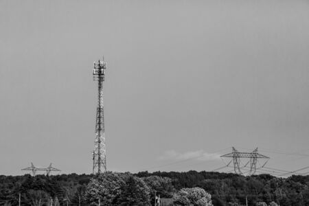 A black and white wide angle landscape with a tall cell site tower, and steel lattice electric pylons over tree tops, city supply and infrastructure.