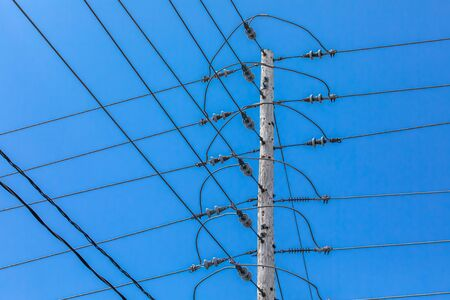 A low angle view of a tall wooden utility pole supporting overhead electric voltage cables with insulators, crossing t-junction lines against a bright blue sky. Фото со стока