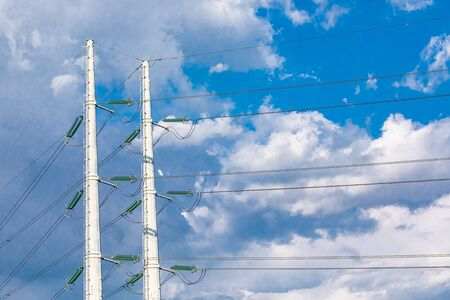 Two utility poles are viewed from below, supporting overhead electric cables, medium voltage cables fixed to tall white pylons against a cloudy skyscape.