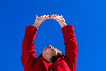 A low angled view of a young Caucasian woman reaching her arms up towards a bright blue sky, enjoying freedom and sunshine on a wintry day. 写真素材 - 132958075