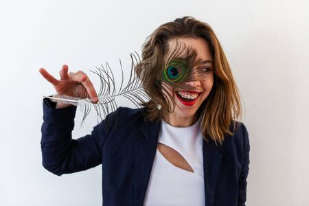 A close up and front portrait of a flirtatious brown haired woman standing against a white background, holding a peafowl tail over one eye and laughing.