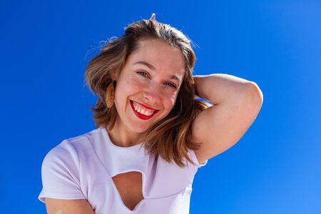 A closeup portrait of a young Caucasian woman with brown hair and a wide smile, holding one hand behind her head, against a clear blue sky. 写真素材 - 132958089