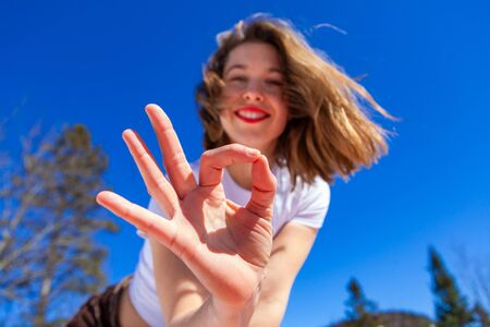 A young Caucasian lady is seen close up, giving the okay hand gesture, joyful to be outdoors with nature during a sunny day with a clear blue sky. 写真素材
