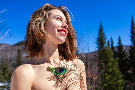 A beautiful Caucasian lady is seen close-up topless, standing in the mountains holding a peafowl tail and looking towards the side. Happy outdoors with nature.