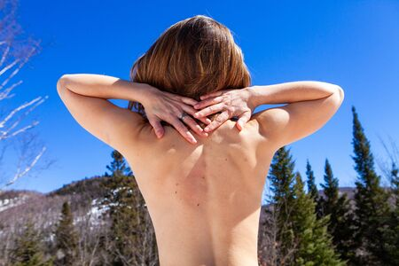 A young Caucasian woman is seen nude from behind stretching her arms behind her head as she sits in front of scenic mountains. Relaxing outdoors in nature.