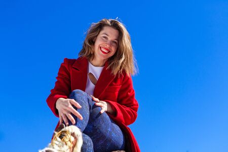 A low angle view of a pretty brunette lady sat outside on a wintry day, wearing a long red coat and blue denim trousers, she smiles widely and looks to camera. 写真素材 - 132958387