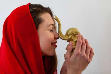 A closeup and side profile view of a confident young Caucasian girl wearing a red headscarf. She holds a golden elephant ornament to bring wisdom and prosperity