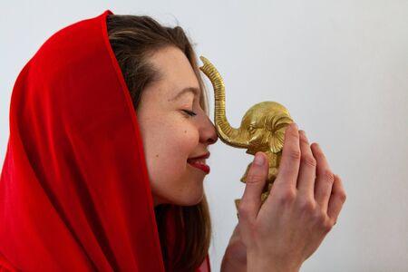 Gros plan et vue de profil d'une jeune fille caucasienne confiante portant un foulard rouge. Elle tient un ornement d'éléphant doré pour apporter sagesse et prospérité
