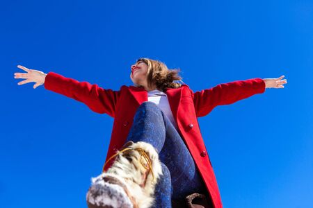 A happy Caucasian woman looks overjoyed with her arms raised against a bright blue sky, wearing a winter coat and boots, shot from a low angled perspective. 写真素材 - 132958435