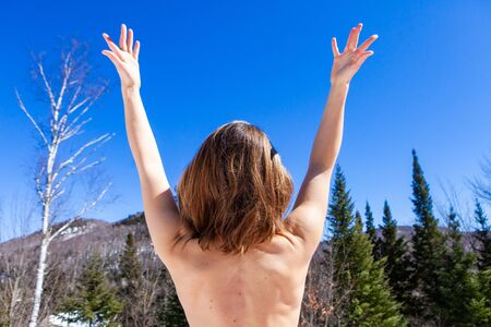 A nude Caucasian lady is viewed from behind doing relaxing arm stretches in a quiet mountain spot. Meditation and relaxation in a natural setting. Stock Photo