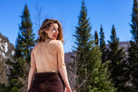 A playful shirtless Caucasian lady is viewed from behind in a mountain woodland beneath a blue sky, she looks over her shoulder a flirtatious manner.