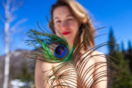 A close-up view of a peacock tail, held be a young Caucasian lady standing topless against a scenic mountain landscape with blue sky. Nude woman in mountains.