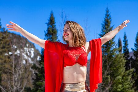 A beautiful and successful young lady is viewed standing by pine trees and mountains. She wears red lingerie and scarf and raises her arms, embracing femininity Banco de Imagens