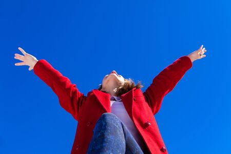An elated Caucasian woman, wearing a red coat, has her arms in the air with joy on a bright winters day against a blue sky, shot from a low angle perspective.