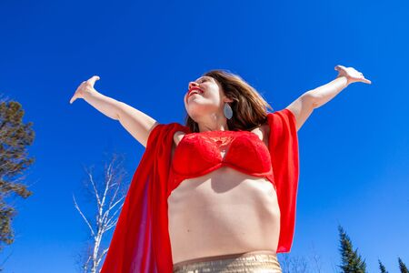 A successful and spirited young Caucasian woman is standing beneath a blue sky wearing sexy lingerie, she raises her arms to celebrate being free in nature. Banco de Imagens