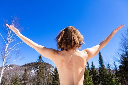 A naked woman is viewed from behind, stretching her arms out towards a mountainous landscape. Overjoyed to be at one with nature on a sunny day. Stock Photo