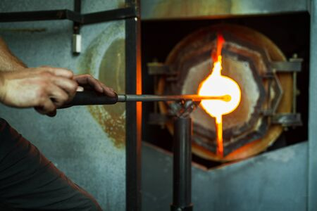 Man is putting his glass in the industrial oven to warm the glass a bit more. Stock Photo
