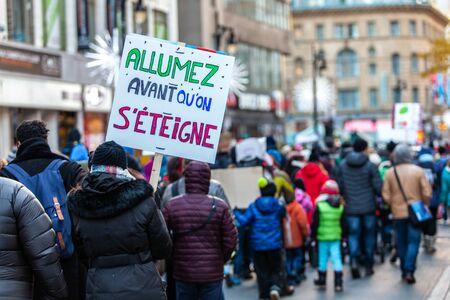 Panneau français vu dans une manifestation écologique disant Allumez avant d'éteindre