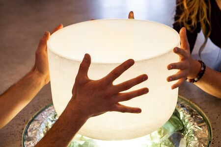 4 hands holding a big crystal bowl on top of a light source as part of a recharging meditation ritual