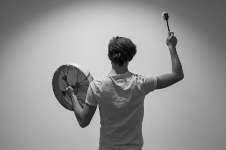 Young man pictured from the back is holding his sacred drum in a hand and raises his drumstick with the other. In the spotlight