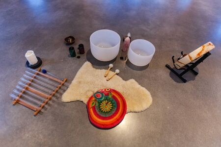 Various sacred objects music instruments like stones, statues, drums, crystal bowls and more are displayed in a set-up on a hard floor, seen from behind Stockfoto