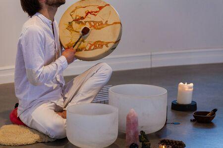 Homme vêtu de blanc, assis sur une peau de mouton et jouant avec un tambour sacré avec divers objets exposés comme des pierres, des bougies et plus
