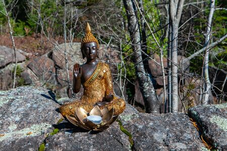 With lantern candle in lotus flower displayed on a rock. Picture taken in Quebec, Canada, on a very warm autumn day